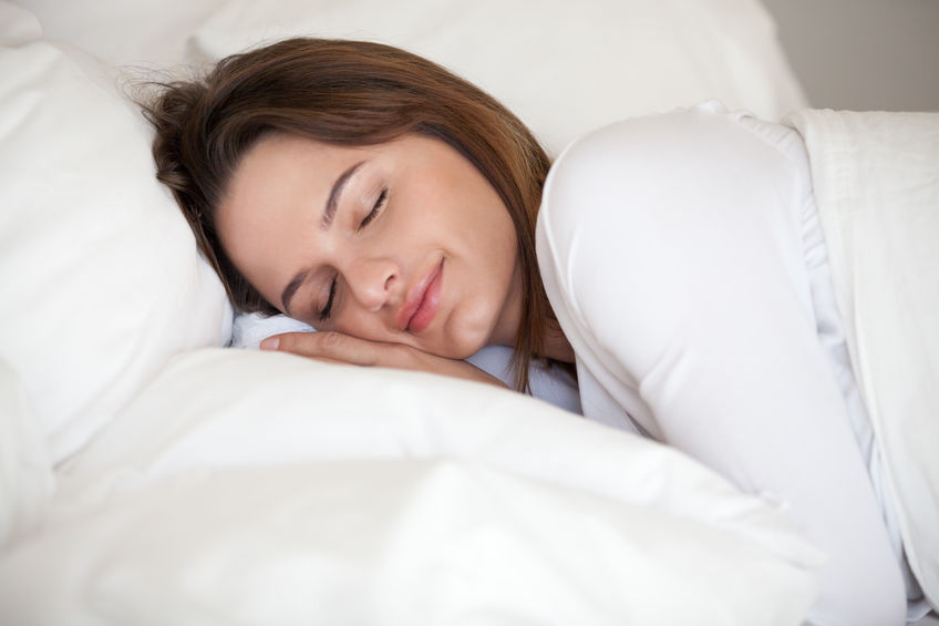 Healthy girl lying asleep on white sheets resting at home