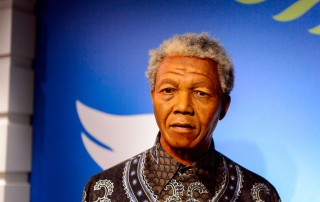 Nelson Mandela pictured in front of blue background.