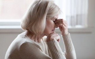 Fatigued older woman faces anxiety.