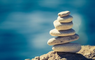White pebbles stacked and carefully balanced over a blue sea