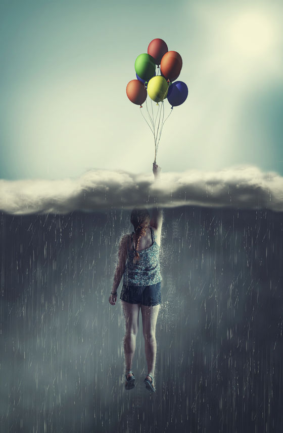 Woman flying with balloons through a rainy cloud to the sunny sky