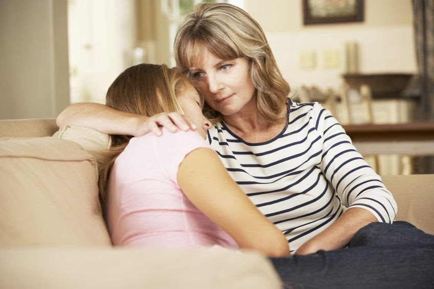 Mother comforts daughter with a caring hug on the couch at home