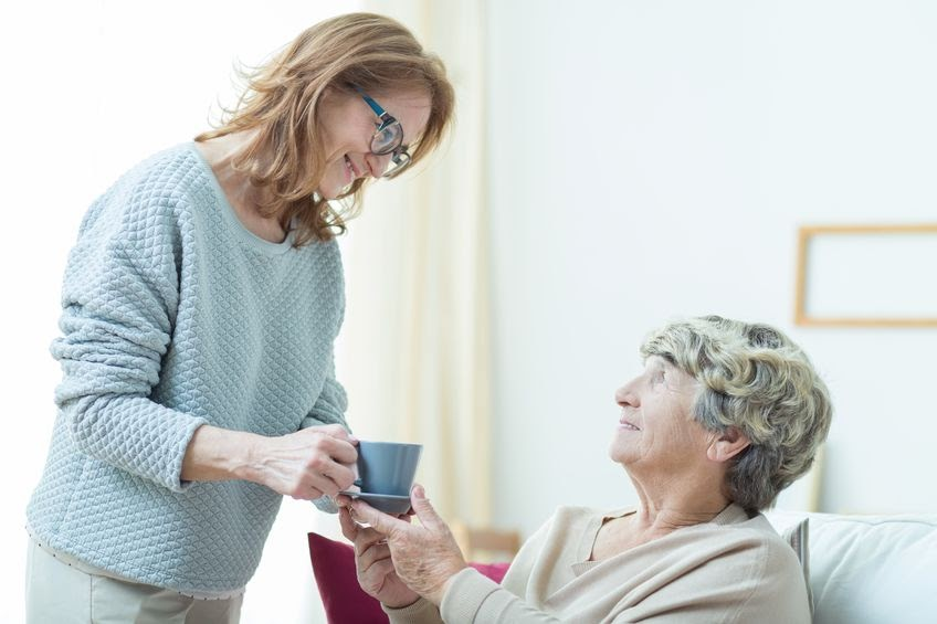 Middle-aged lady smiles as she hands a mug to an elderly woman sitting in bed